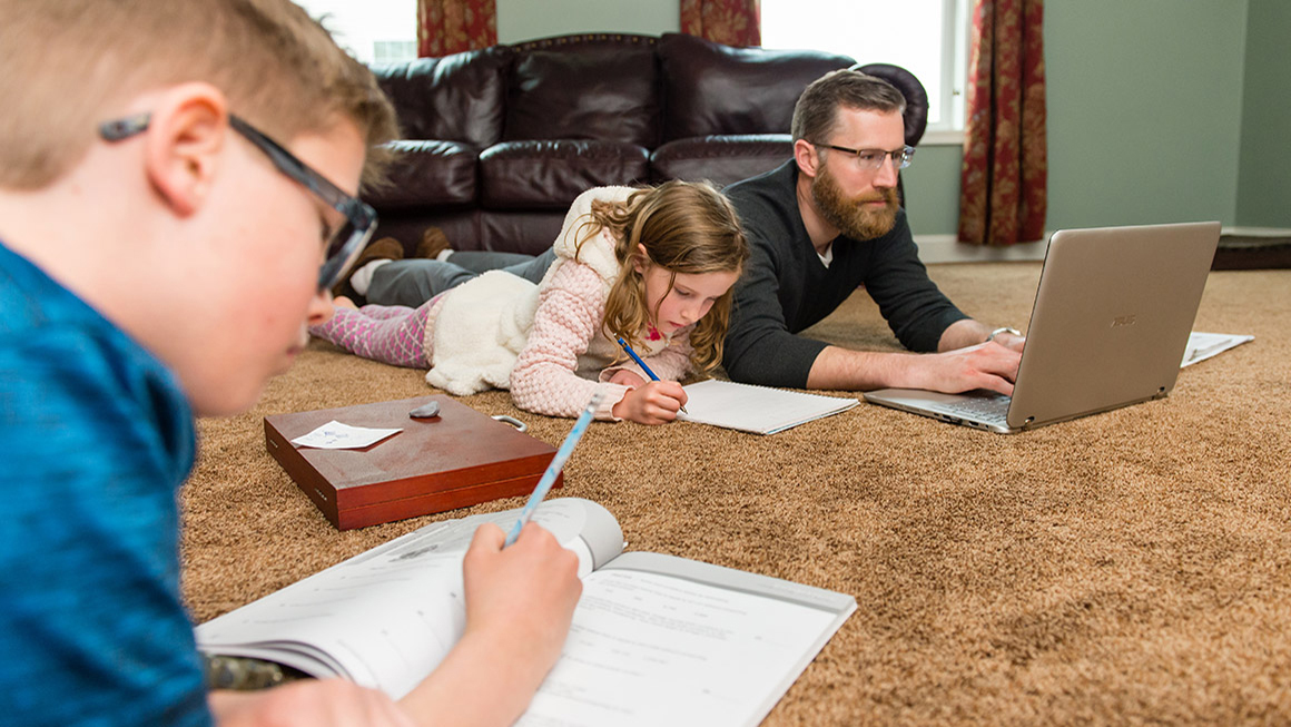 Aaron Spak on the floor, working at his computer, with his children