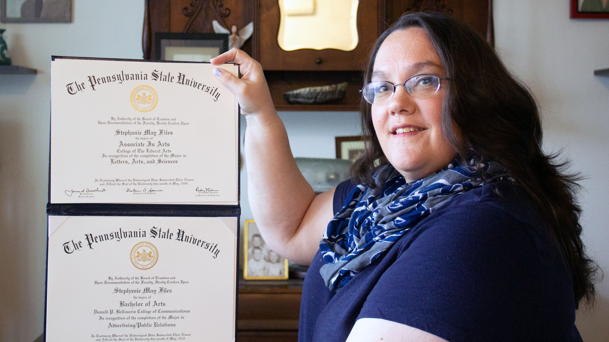 Stephanie Files displays two diplomas in her hands
