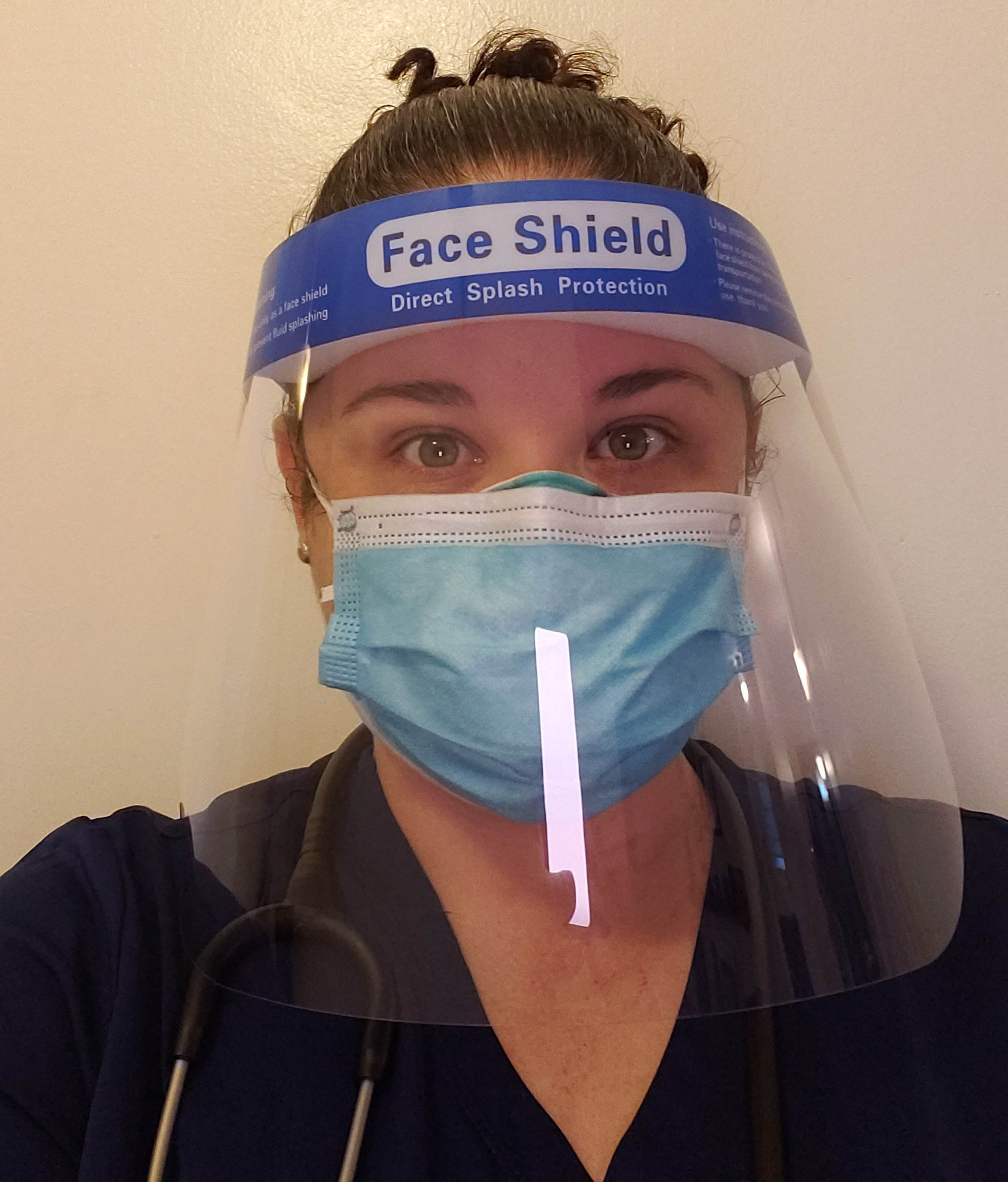A nurse is seeing wearing a face shield and mask