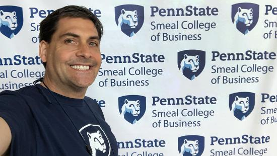 Bussey takes a selfie in front of a Penn State backdrop.