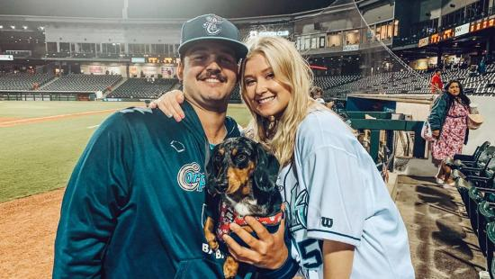Kylie Smith is shown with her fiance at a baseball stadium.