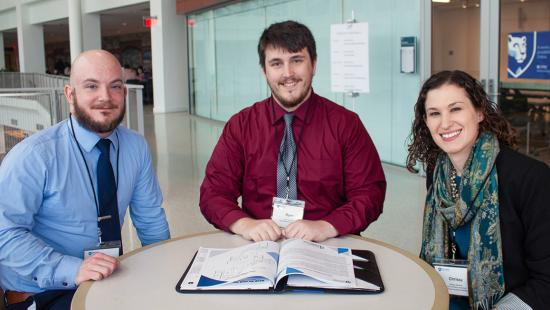 Three Penn State World Campus students are seen at a table after a session at the student leadership conference in 2018.