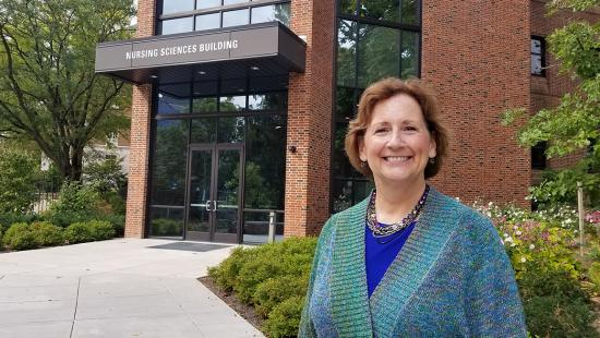 Kelly Wolgast from the Penn College of Nursing is pictured with the entrance to the Nursing Sciences Building in the background