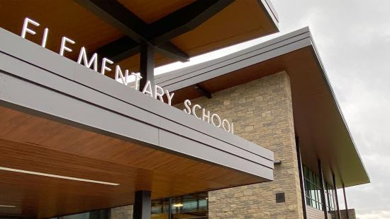 "the words ""elementary school"" are part of a sign on top of the awning of an entrance to a school"
