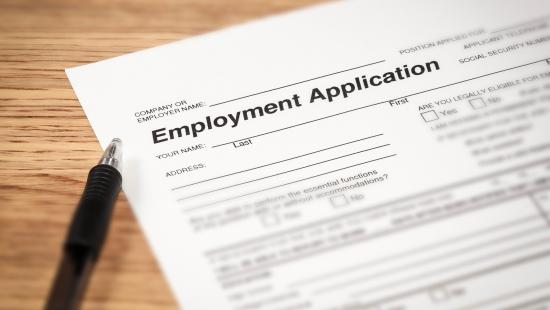 An employment application is shown with a pen on a wooden surface