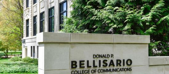 A sign on stone wall shows the name Donald P. Bellisario College of Communications