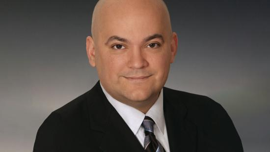Headshot of Mike Russo in a black suit.