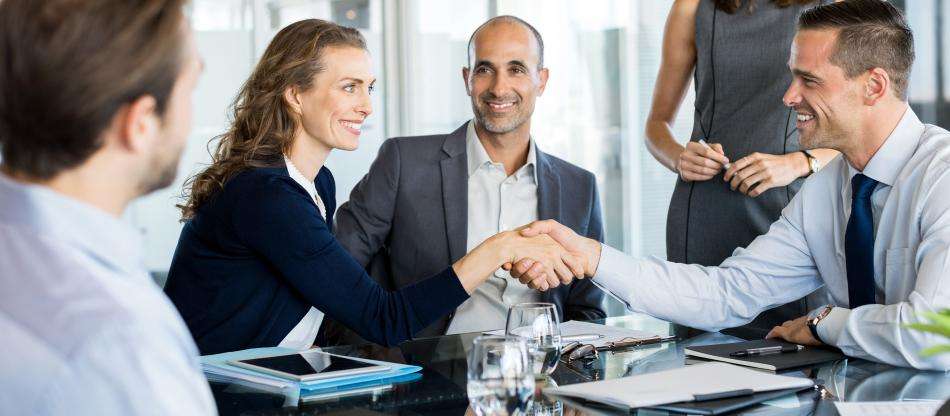 Business professionals shaking hands at a meeting