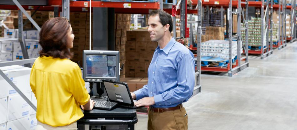 Two professionals working on computers in a warehouse
