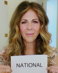 "Actress Rita Wilson holds up a sheet of paper that has the word ""National"" on it."