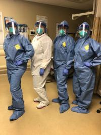 Four nurses wearing protective gear pose.